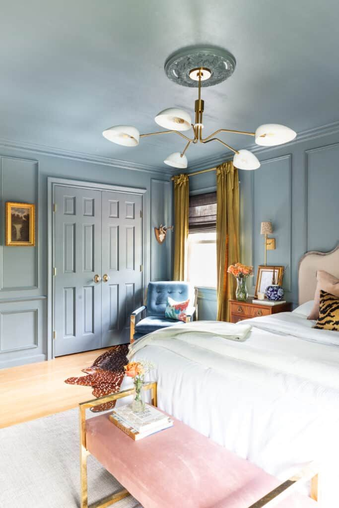 bedroom, wooden floor, blue wainscoting wall, blue ceiling, blue door, modern white pendant, yellow curtain, blue tufted chair, bed, pink bench