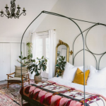 Black Metal Bed Frame With Curvy Vaulted Top, Patterned Rug, Chandelier, Plants, Golden Mirro