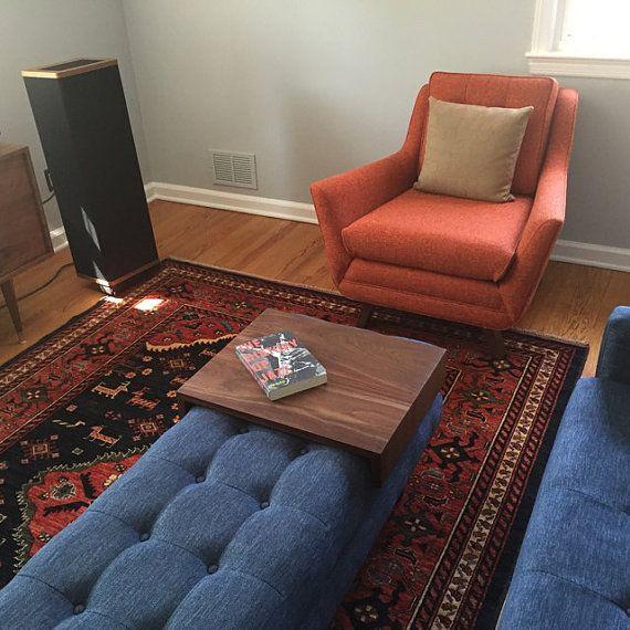 blue tufted rectangular ottoman, wooden sliding tray, patterned rug, orange chair, blue sofa