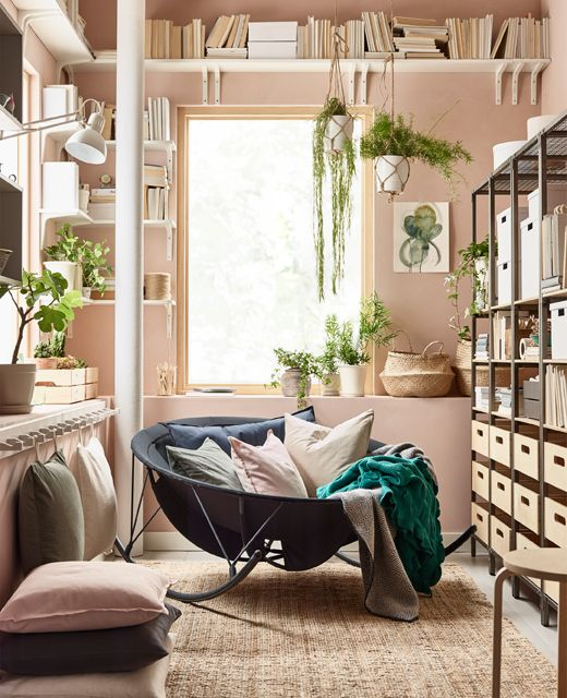 corner, black round rocking chair, cream wall, shelves, rattan rug, pillows, floating shelves