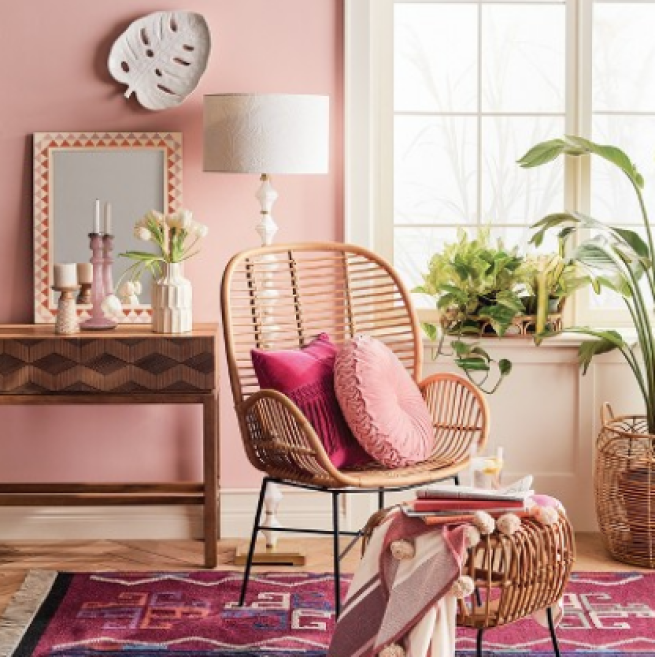 corner room, wooden floor, pink wall, rattan chair, wooden table, mirror, red rug, rattan ottoman