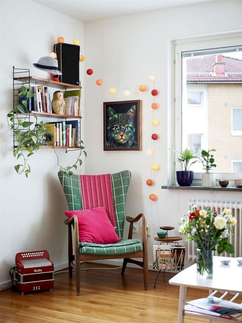 corner room, wooden floor, white wall, white coffee tbale, floating shelves, wooden chair, pink green cushion