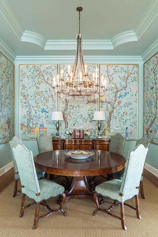 dining room, brown floor, green wall, flowery pattern on the floor, green chairs, round wooden table, chandelier