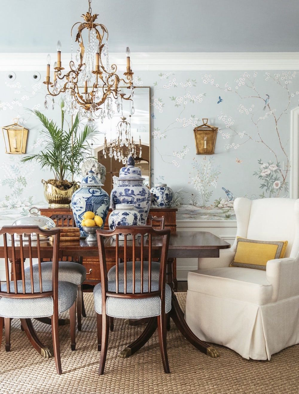 dining room, light blue wall with flowery pattern, wooden table, wooden chairs, white chair, chandelier, mirror