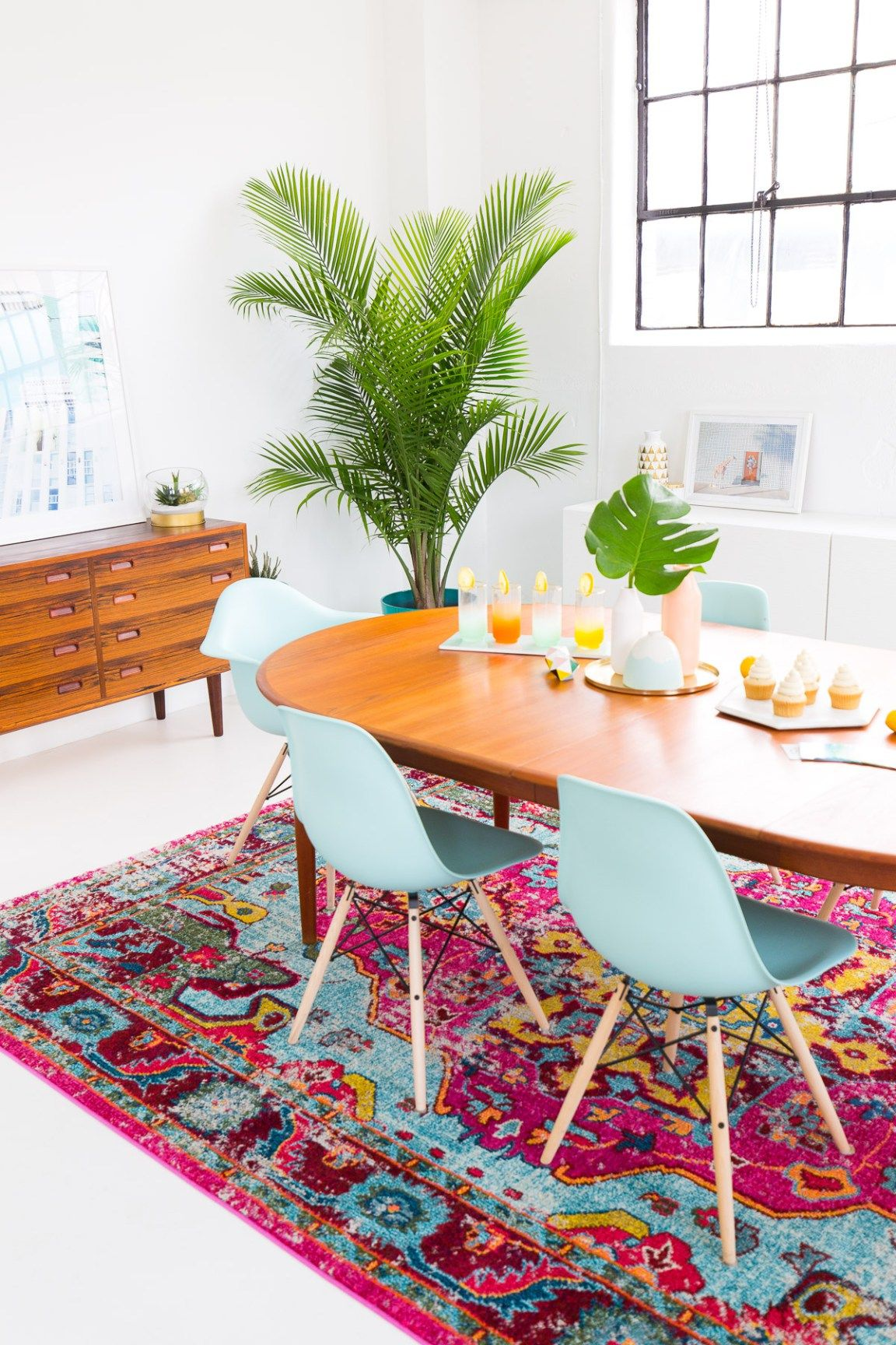 dining room, white wall, white floor, pink patterned rug, blue modern chairs, wooden cabinet, wooden oval table