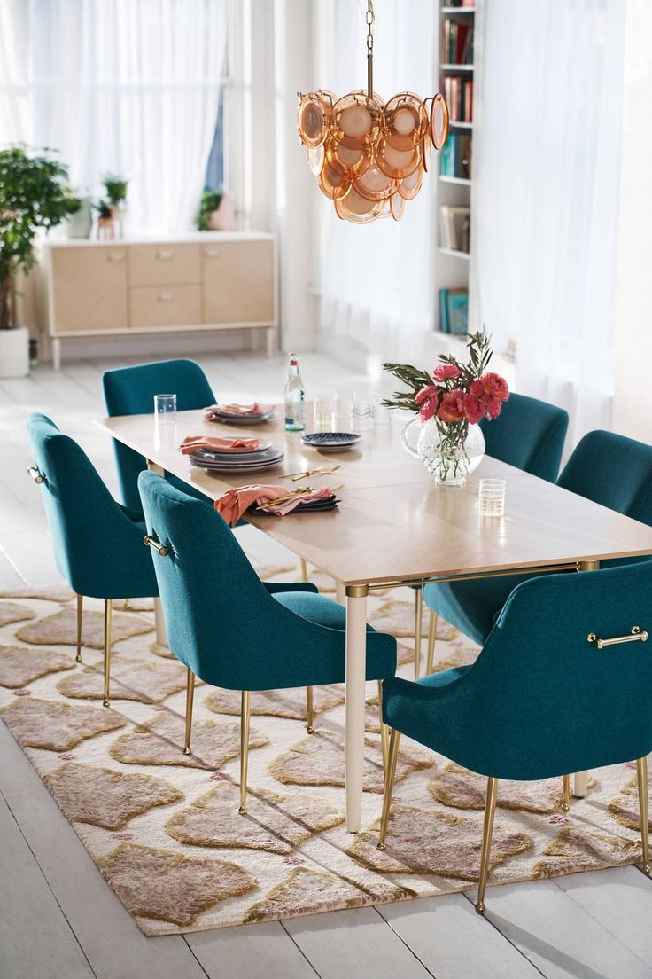 dining room, white wooden floor, teal chairs with golden legs, wooden rectangular table, white wall, golden chandelier