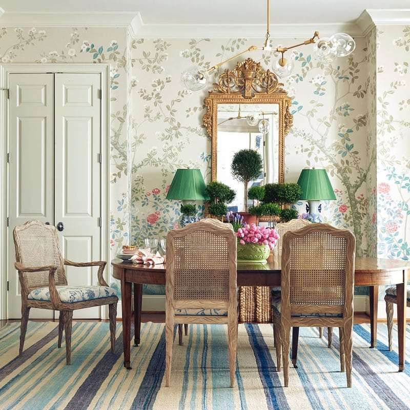 dining room, wooden floor, blue striped rug, wooden table, wooden chairs, flowery wallpaper, golden mirror, green table lamp, glass chandelier