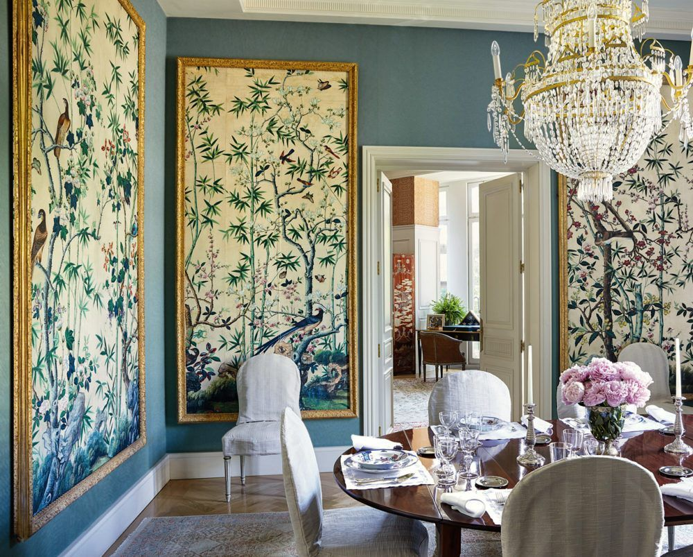 dining room, wooden floor, blue wall, flowery screen painting, crystal chandelier, round wooden table, white table