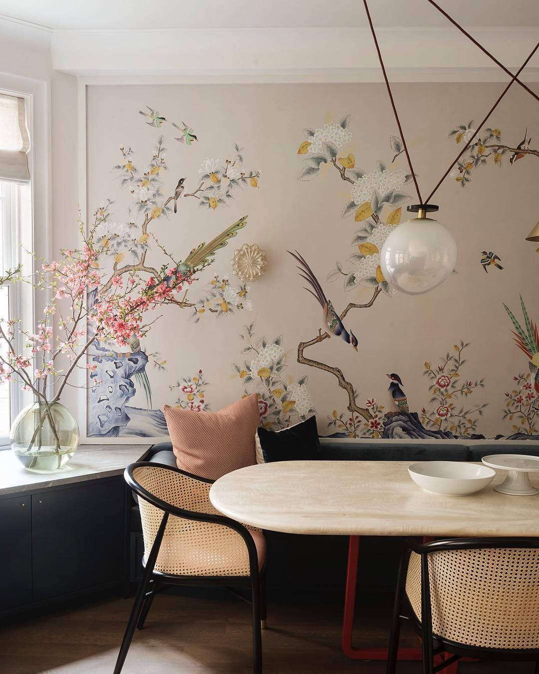 dining room, wooden floor, flowery wallpaper, black cabinet, white marble table, black chairs, grey sofa