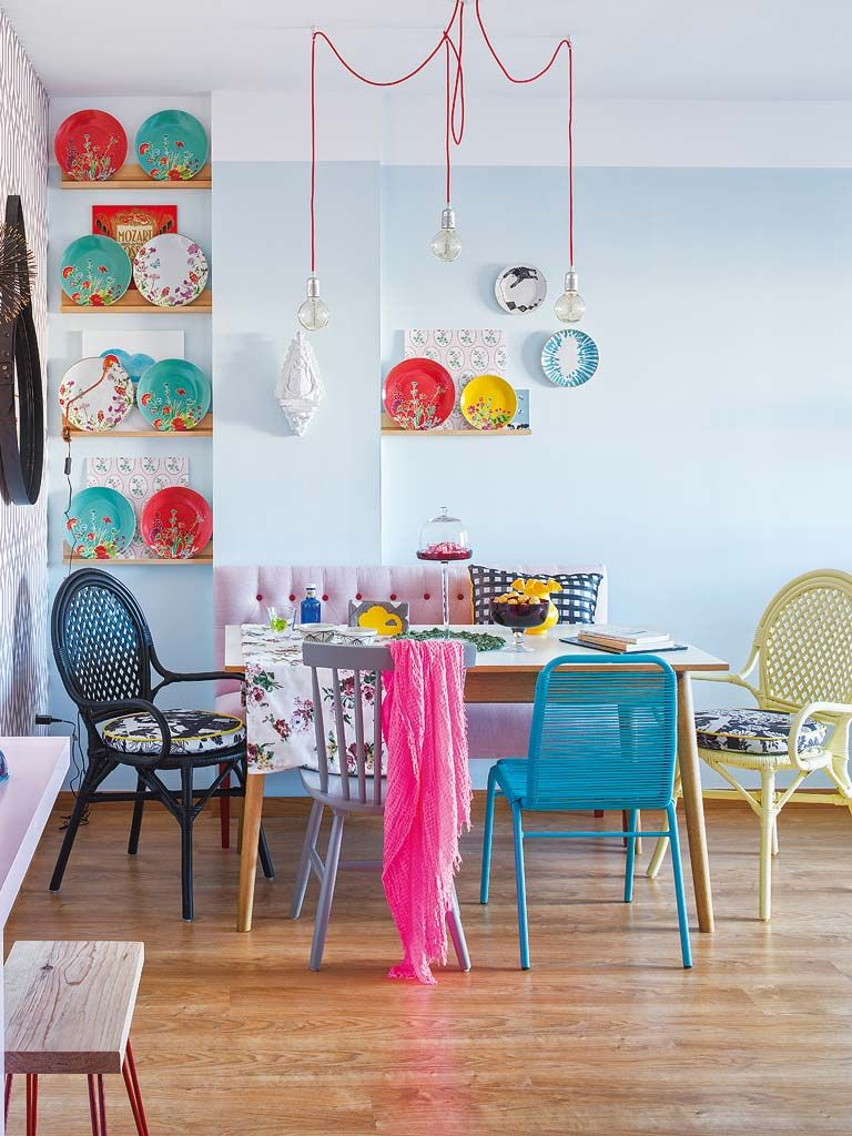 dining room, wooden floor, light blue wall, pink tufted sofa, unmatched chairs, pendant, colorful decorations