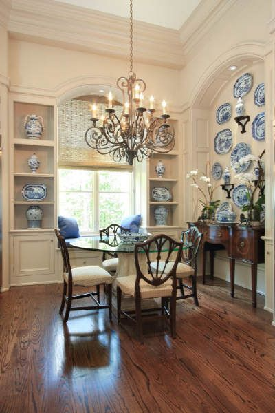 dining room, wooden floor, white wall, indented wall, indented shelves, blue white plates, iron chandelier, glass round table, wooden chairs with white cushion, window seat