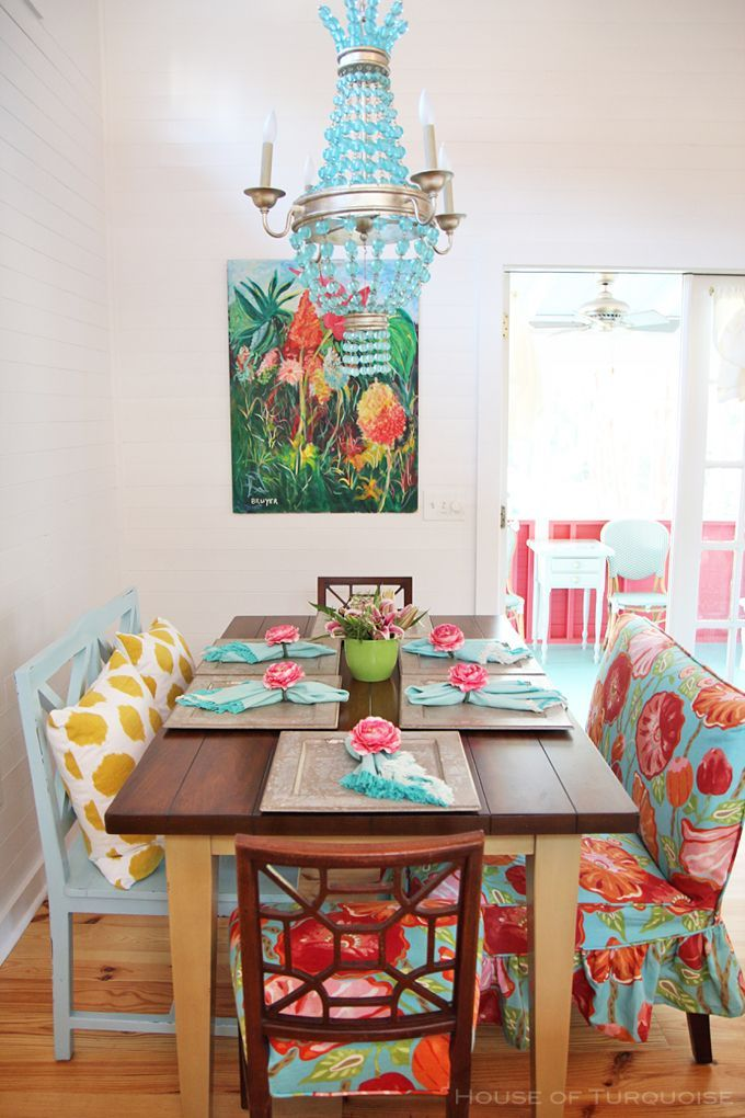dining room, wooden floor, white wall, wooden table, patterned sofa and cushion, blue wooden bench