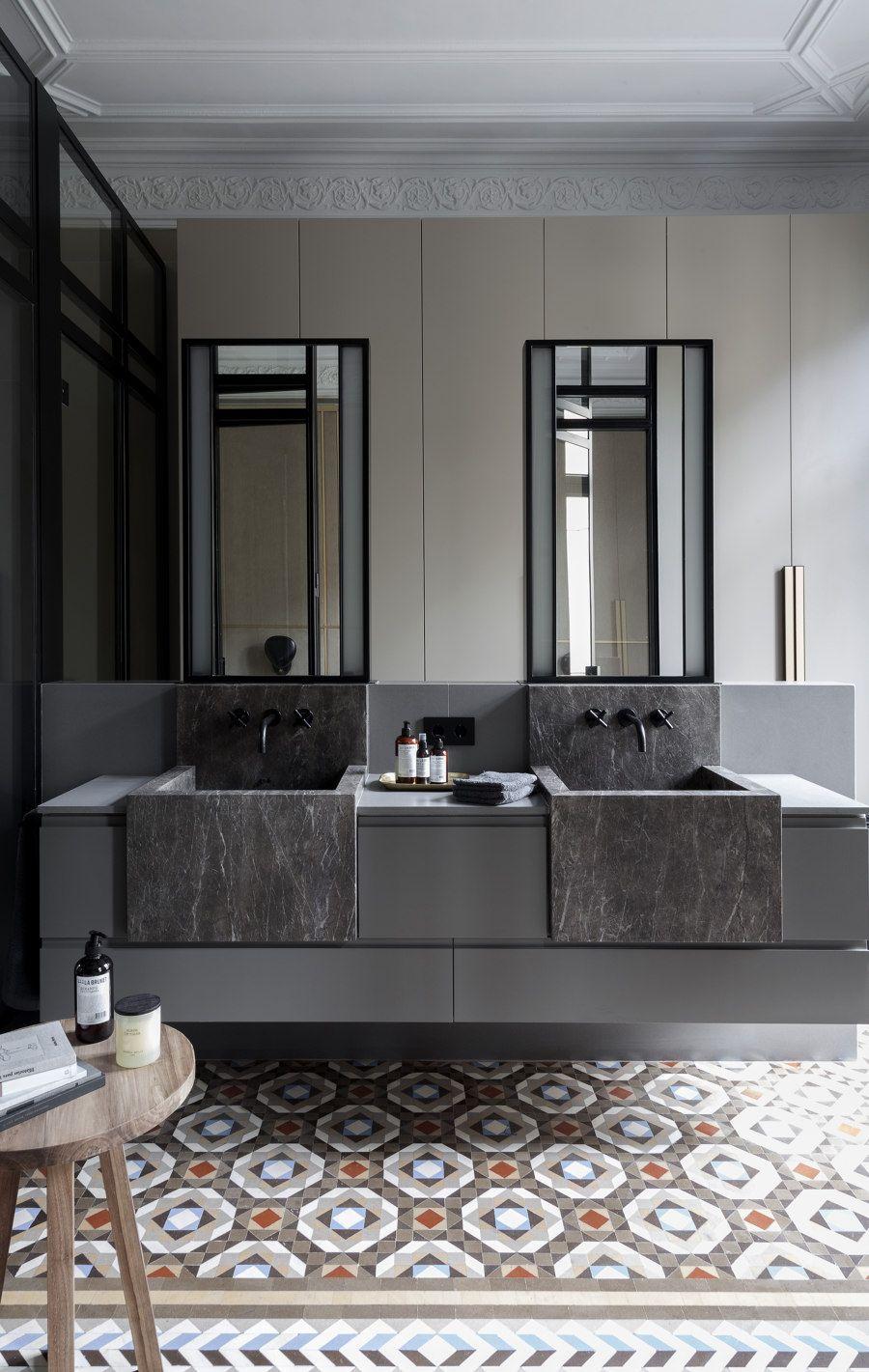grey floating vanity, black marble sink, grey wall, tall mirror, patterned floor tiles, wooden side table