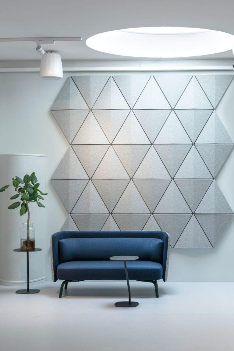 grey geometrical accent wall, bleu sofa, black round side table, white floor
