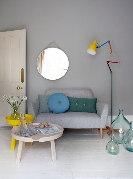 grey wall, white wooden floor, tray coffee tables, colorful floor lamp, grey sofa, round mirror, glass