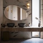 Grey Wall With Fishes, Floating Vanity, Black Round Sink, Golden, Dark Grey Square Floor Tiles, Egg Shaped Mirror, Golden Sconces