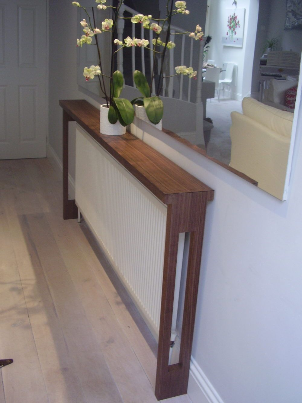 hallway, white wall, narrow wooden console table, white fences, wooden floor, mirror