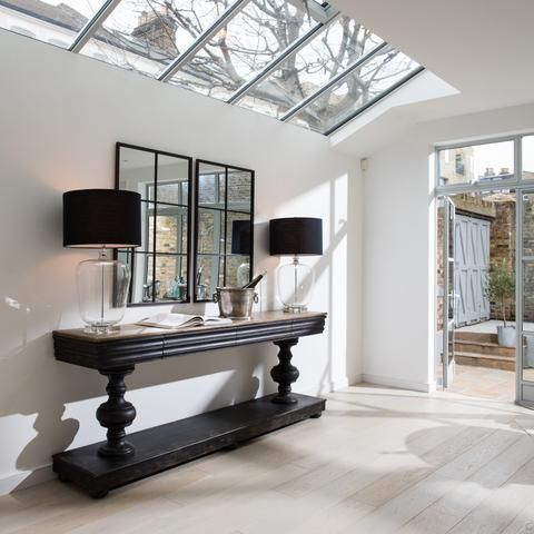 hallway, white wall, white wooden floor, glass ceiling, black console, black cover table lamp, square mirror