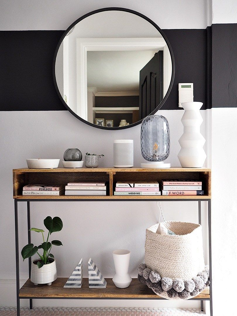 hallway, white wall, wooden console table, opened drawers, shelves, round mirror