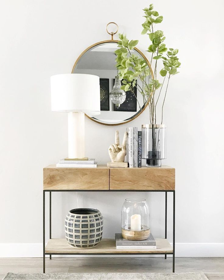 hallway, white wall, wooden floor, wooden console table with drawers, golden framed round mirror, white table lamp