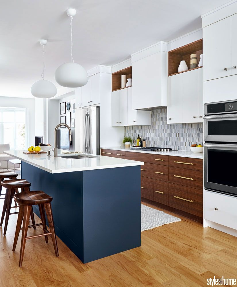 kitchen, wooden floor, white upper cabinet, wooden bottom cabinet, grey backsplash, dark blue island white counter top, white top pendant, wooden stools