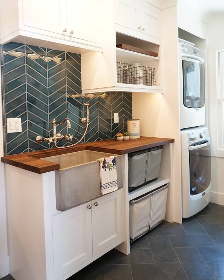 laundry room, dark grey floor tiles, white shelves, white cabinet, vertically stacked white machines, dark grey backsplash, wooden counter top, grey apron sink
