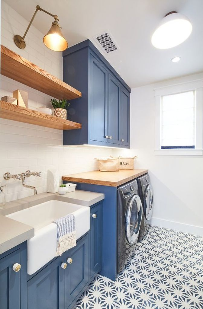 laundry room, patterned floor, white wall, white subway tiles, blue cabinet, wooden shelves, white apron sink