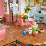 Living Room, Brown Floor Tiles, Ratan Rug, Patterned Rug, Pink Ottoman, Wall White, Yellow And Pink, Round Wooden Coffee Table, Blue Table, Rattan Pots, Plants
