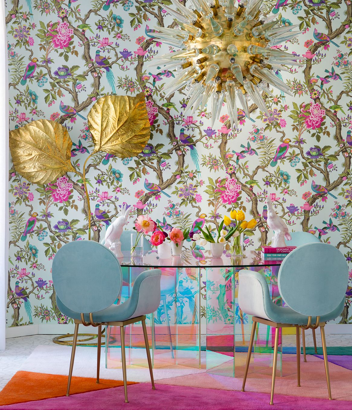 living room, colorful geometrical rug, blue chairs, glass table, flowery wallpaper, golden floor lamp, golden pendant