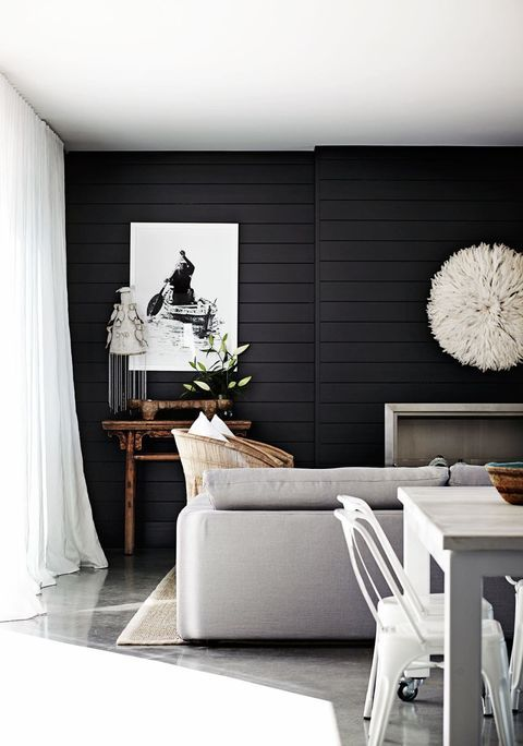living room, concrete floor, grey sofa, black shiplank wall, woode side table, fireplace