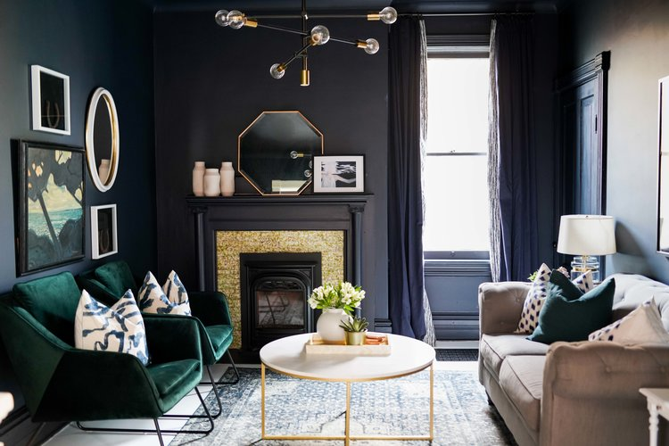 living room, dark blue wall, dark green chairs, brown sofa, round white coffee table,rug, modern chandelier, fireplace