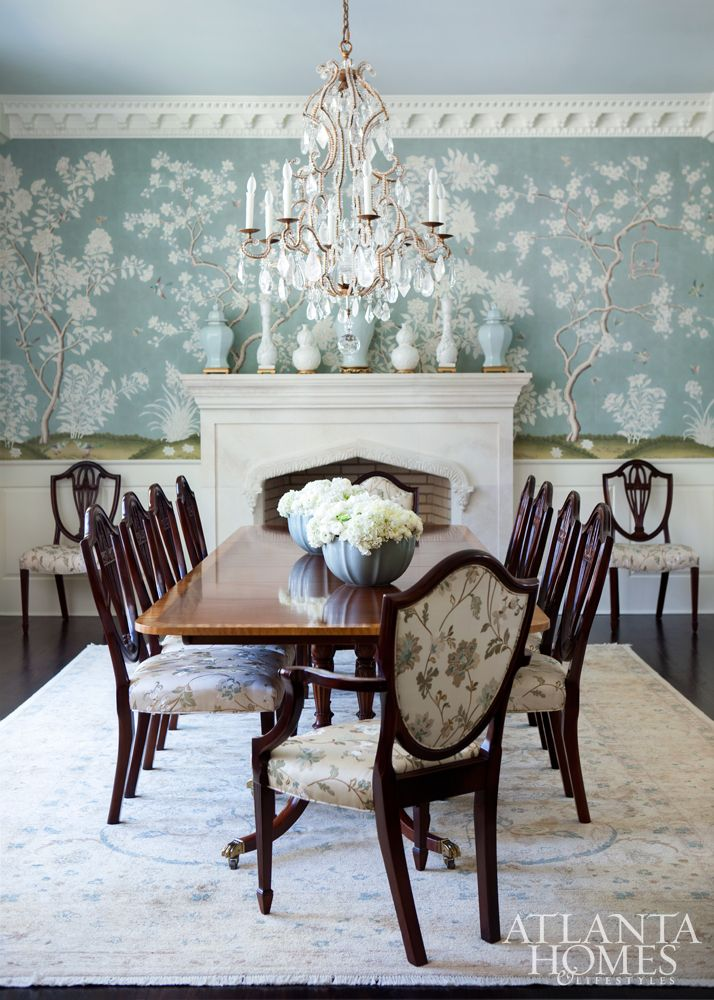 living room, dark wooden floor, white patterned rug, wooden chairs, flowery cushion, green flowery wallpaper, white fireplace, chandelier