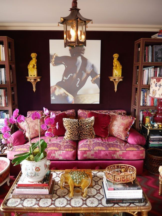 living room, patterned rug, pink sofa, dark red wall, accessories, wooden shleves