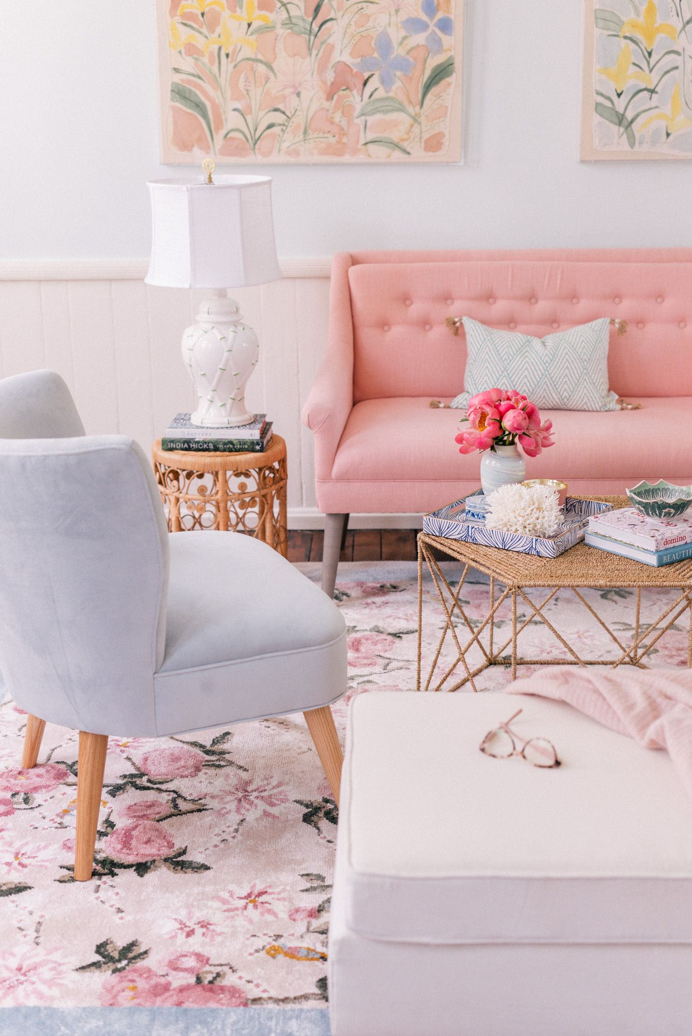 living room, pink flowery rug, white ottoman, grey chair, pink sofa, rattan coffee tbale, rattan side table, white wainscoting