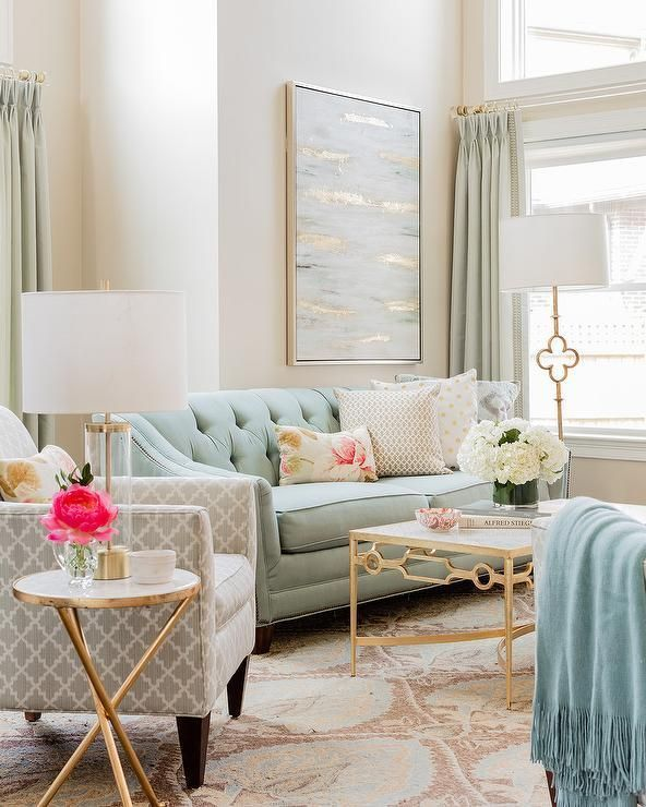 living room, pink patterned rug, blue tufted sofa, grey chairs, golden framed side table, white coverred table lamp, golden framed coffee table, white covered floor lamp