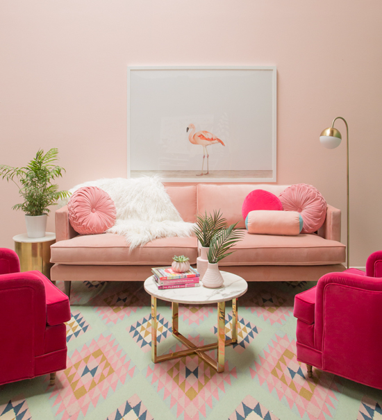 living room, pink wall, pink patterned rug, soft pink sofa, shocking pink chairs, golden floor lamp, golden side table, golden framed round coffee table
