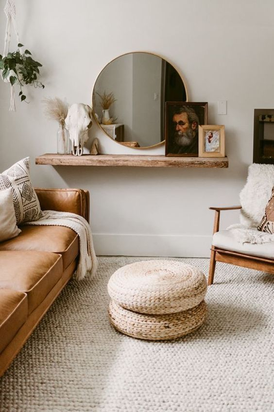 living room, rattan rug, brown leather sofa, wooden chair, white cushion, rattan ottoman, white wall, floating wooden shelves, round mirror