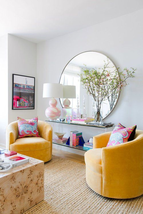 living room, rattan rug, white wall, floating glass shelves, yellow chair, wooden coffee table, white table lamp, round mirror
