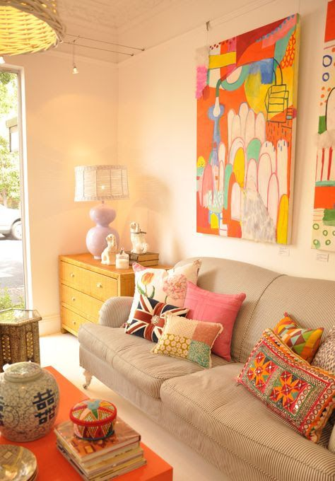 living room, white wall, grey sofa, wooden cabinet, wooden table, white table lamp, colorful pillows
