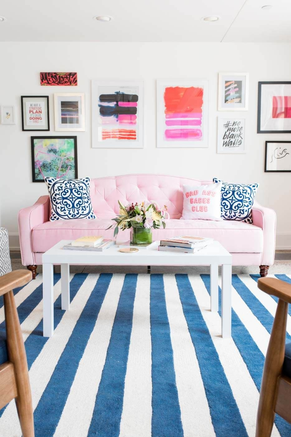 living room, white wall, pink sofa, blue white striped, wooden chairs, white wooden coffee table