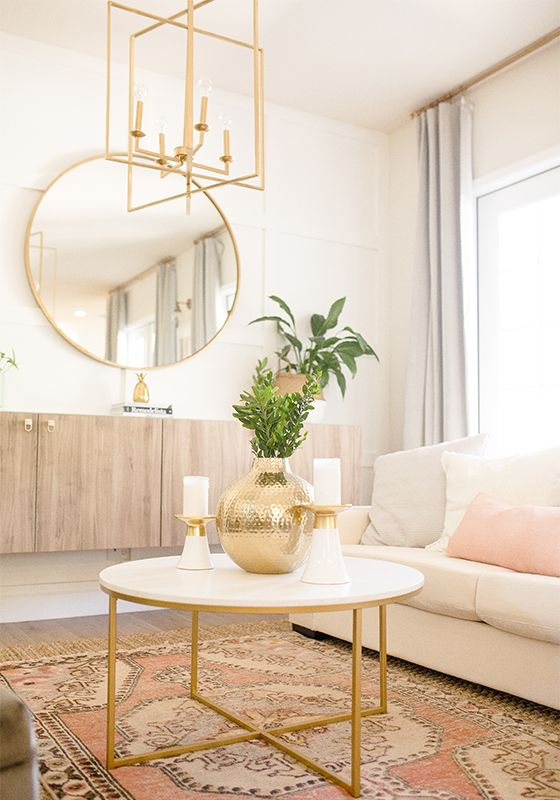 living room, white wall, red rug, white round coffee table with golden feet, white sofa, floating wooden cabinet