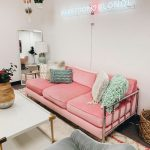 Living Room, White Wall, Silver Iron Sofa With Pink Cushion, White Coffee Table, Grey Chair, Mirror, Table Lamp