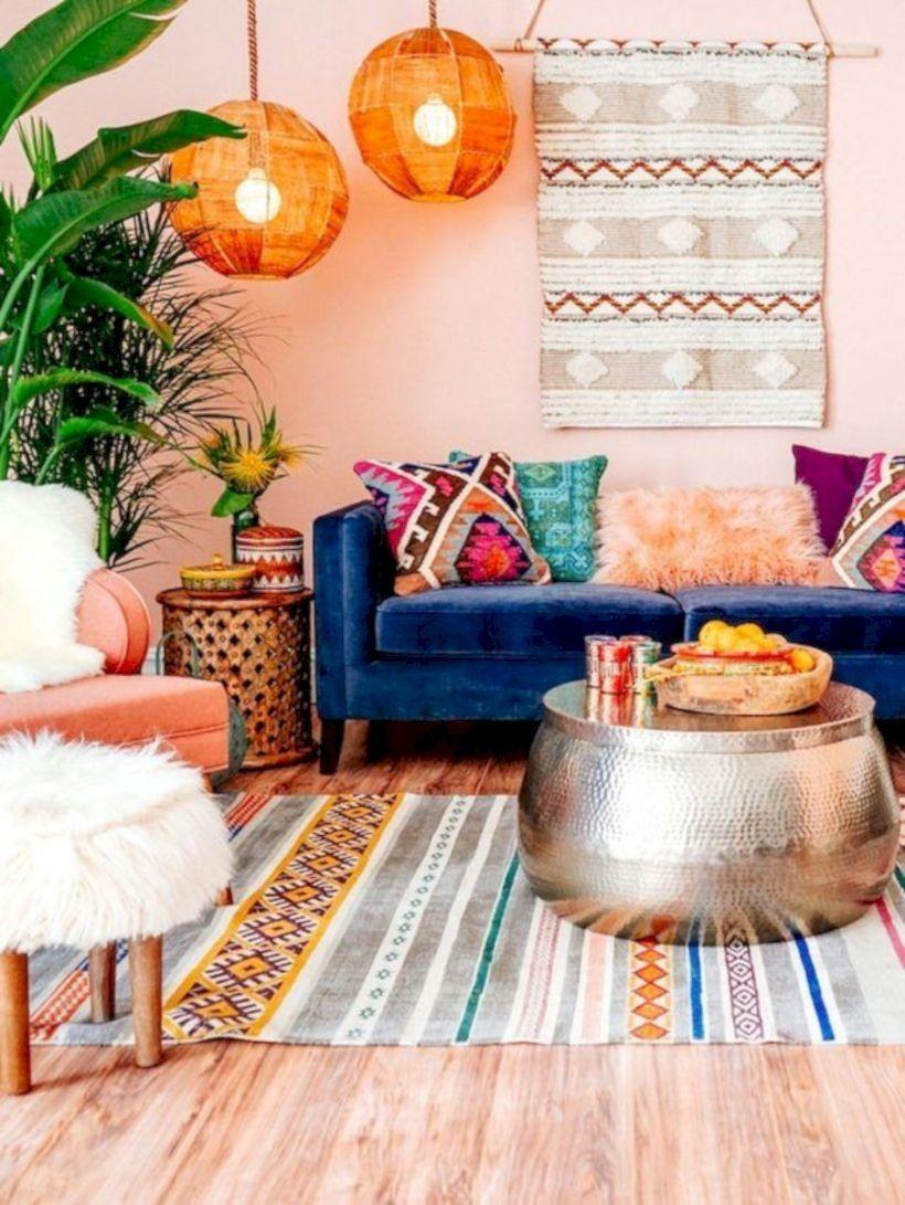 living room, wooden floor, pink cream wall, patterned rug, silver ottoman, blue velvet sofa, orange chair, white fur ottoman, orange ball pendants