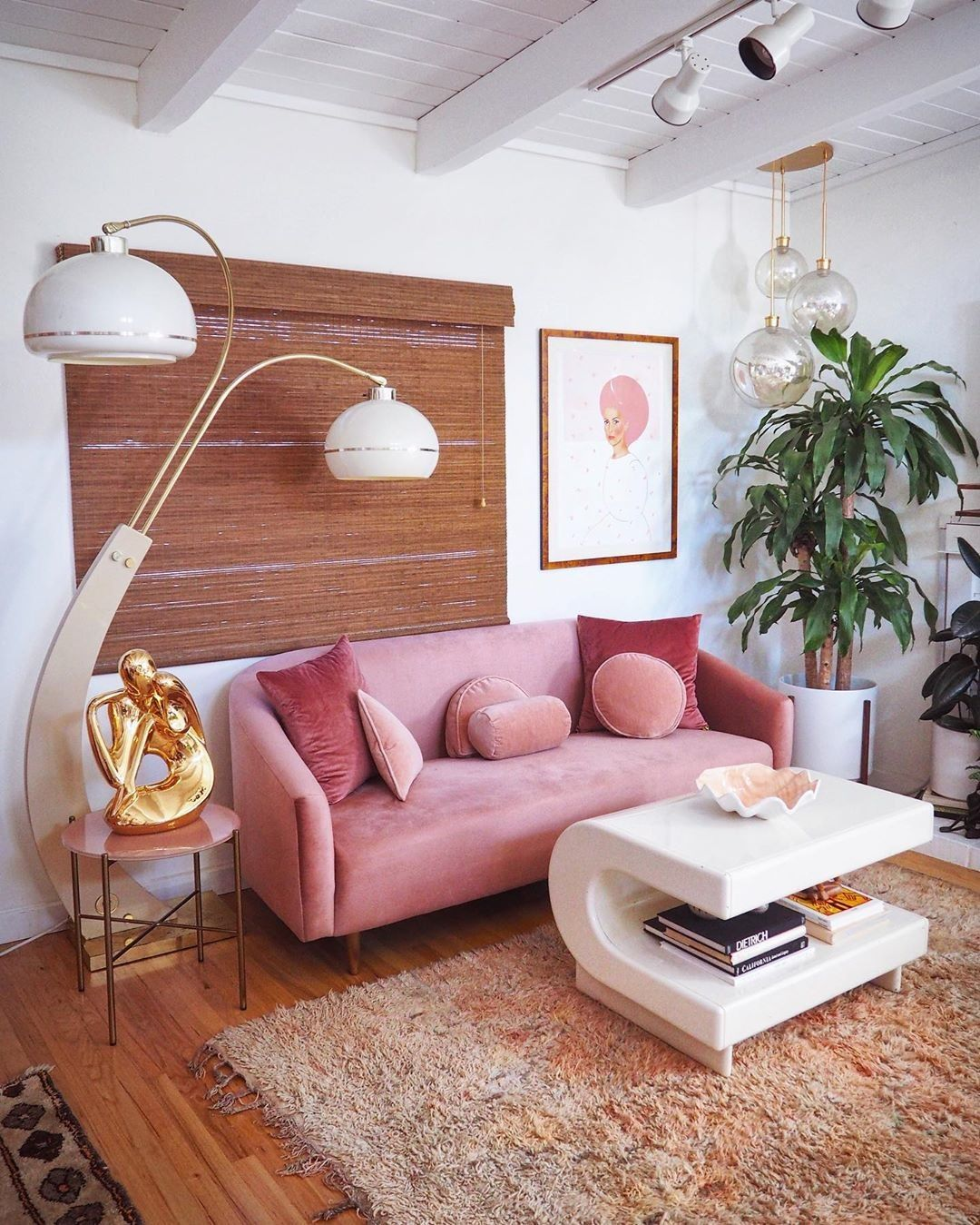 living room, wooden floor, white wall, curvy floor lamp, pink velvety sofa, pink side table, glass pendants, white C shaped coffee table, brown rug