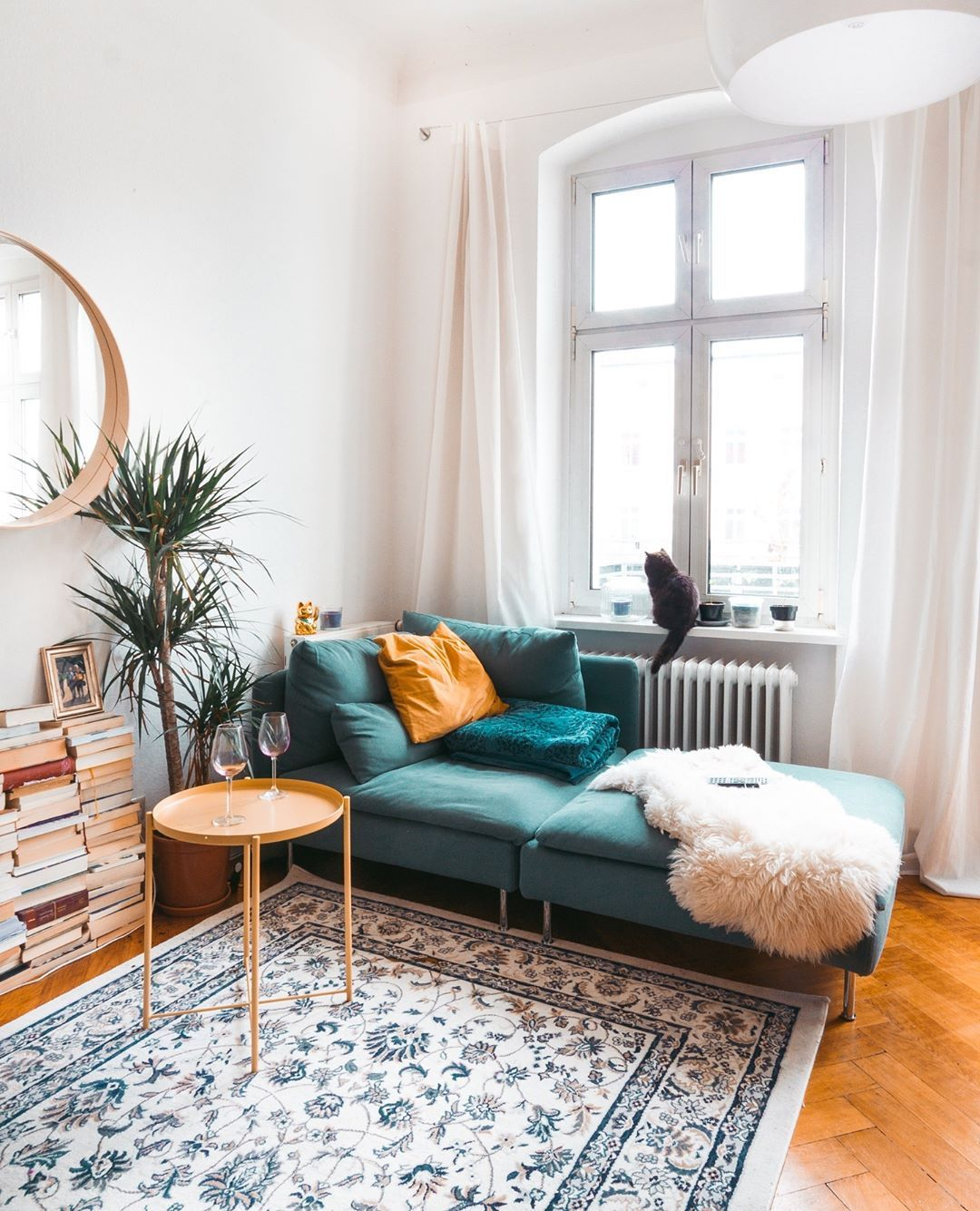 living room, wooden floor, white wall, green lounge chair, wooden tray side table, wooden mirror