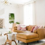 Living Room, Wooden Floor, White Wall, Modern Chandelier, White Accent Wall, Brown Leather Sofa, White Rug, Rattan Rocking Toy, White Round Coffee Table