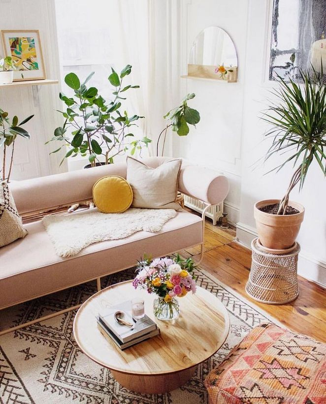 living room, wooden floor, white wall, pink bench, white patterned rug, mirror, plants, wooden round coffee table