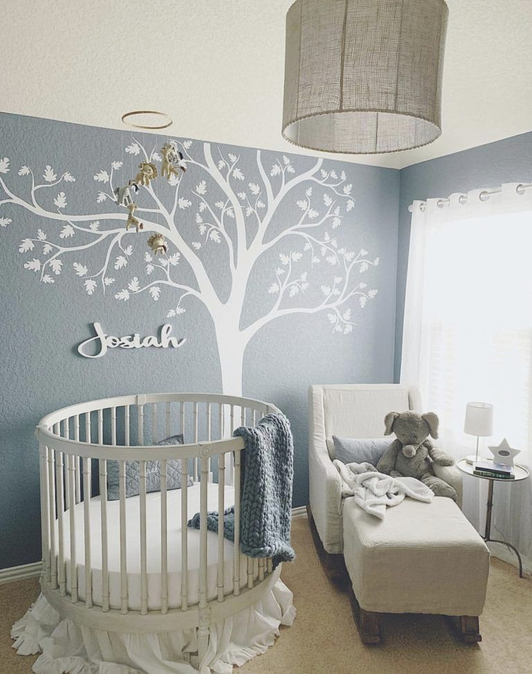 nursery, brown floor rug, blue wall, white lounge chair, white round crib, round pendant