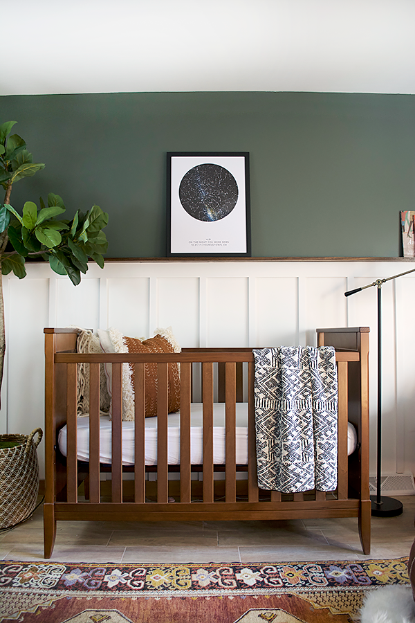 nursery, brown marble floor tiles, green wall, white wainscoting, wooden crib, patterned rug