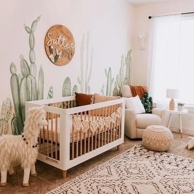 nursery, brown marble floor tiles, patterned rug, white wall, cactus painting, round ottoman, white chair, wite round chair